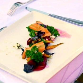 De la salade aux carottes rôties, betteraves et fromage de chèvre déposée dans une assiette blanche.