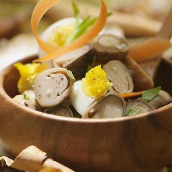 Des coprins, un morceaux d'œuf à la coque, un ruban de carotte dans un bol en bois.