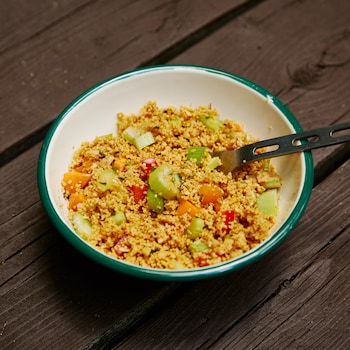 Sur une table en bois, est déposé un bol rempli de salade de couscous aux légumes. Il contient une cuillère en métal.