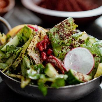 Un bol de salade fattouche garni de radis, de concombres et de grenade.