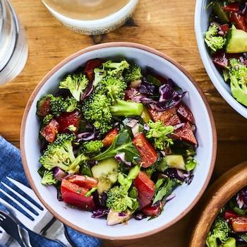 Bols de salade de légumes posés sur un comptoir de bois.