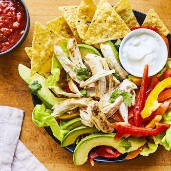 Assiette de salade de poulet grillé façon fajitas avec salsa en accompagnement.