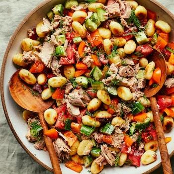 Il est possible de voir un grand bol contenant la salade de gnocchis au thon et deux grandes cuillères de bois sur une table avec une nappe verte pâle.