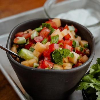 Un bol de salsa de tomates et cantaloup entouré de coriandre fraîche et de condiments.