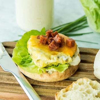 Un sandwich déjeuner dans un muffin anglais sur une planche de bois.