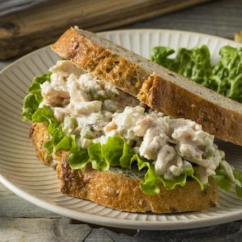 Une assiette contenant un sandwich au poulet garni d'une feuille de laitue.