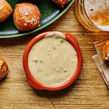Il est possible de voir sur une table de bois, un bol contenant la sauce au fromage. Autour, nous pouvons voir des bouchées de bretzel et un verre de bière.