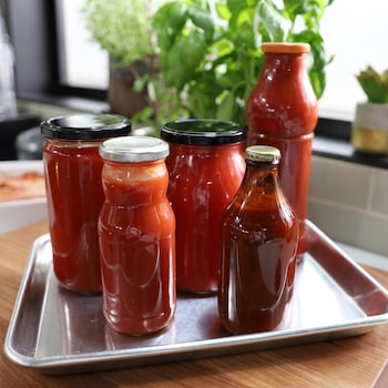 Des bouteilles en verre de différents formats remplis de sauce tomate.
