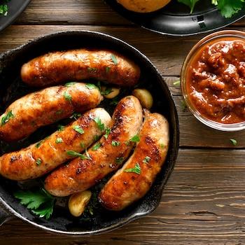 Cinq saucisses dans une poêle avec un petit bol de salsa.
