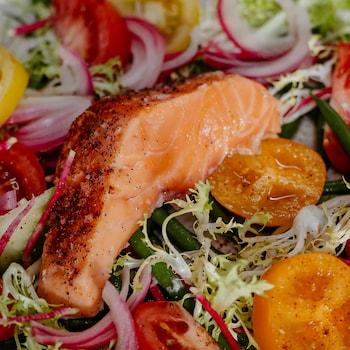 Un morceau de saumon confit, servi sur un lit de verdure, de tomates et d'oignons marinés.