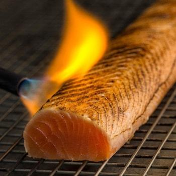 Un filet de saumon qui se fait caramélisé au chalumeau.