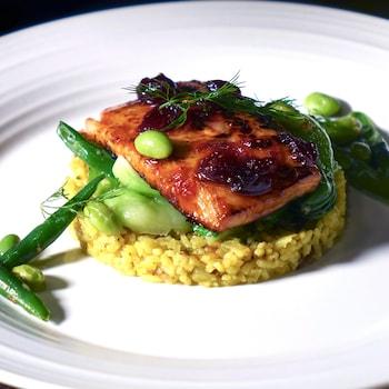 Un morceau de saumon laqué déposé sur du riz pilaf persan et des légumes verts.