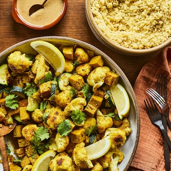 au centre d'une table en bois est déposé une assiette du sauté de chou-fleur et de tofu à la marocaine.