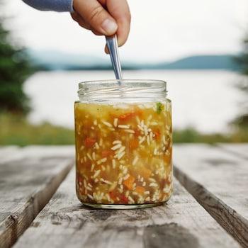 Un pot en verre, contenant de la soupe au jerky et au riz, est déposé sur une table en bois. Un main est au-dessus du pot en verre et elle tient la cuillère qui est dans le pot.