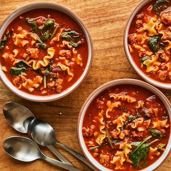 Sur une planche en bois est déposé trois bols et trois cuillères. Les bols sont remplis de soupe-lasagne.