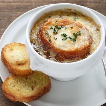 Une bol de soupe à l'oignon gratinée dans une assiette avec deux morceaux de pain.
