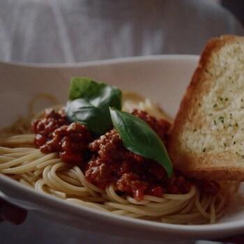 Un bol de spaghetti, garni de sauce bolognaise et de basilic frais, accompagné d'une tranche de pain à l'ail.