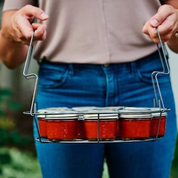 Sriracha maison dans de petits pots. Ceux-ci sont insérés dans un panier.
