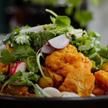 Une assiette de tajine de tofu aux olives et au citron confit, servie sur de la purée de chou-fleur et garnie d'herbes fraîches.