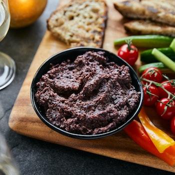 Bol de tapenade aux olives Kalamata sur une planche de bois avec des légumes, du pain grillé et une coupe de vin blanc.