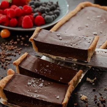 Une tarte au chocolat de forme rectangulaire tranchée et servie avec des petits fruits.