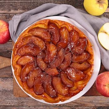Une tarte tatin entourée de quelques pommes.