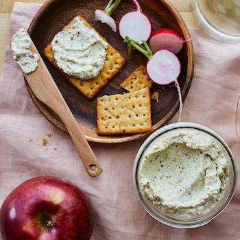 Sur un napperon rose est déposé une pomme, un bol de tartinade de tofu à l'aneth et des craquelins.