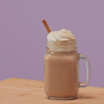 Une tasse en vitre contenant du thé chaï avec de la crème fouettée et un bâton de cannelle.