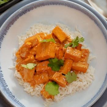 Du tofu au beurre servi sur un lit de riz basmati et garni de feuilles de coriandre.