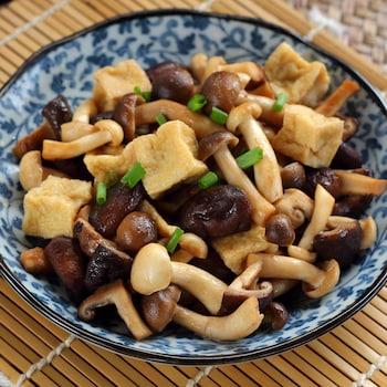 Un bol rempli de morceaux de tofu et de champignons.