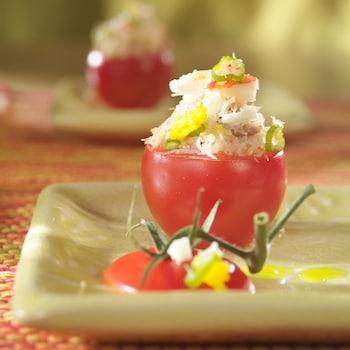 Des tomates du jardin farcies au crabe des neiges dans des assiettes.