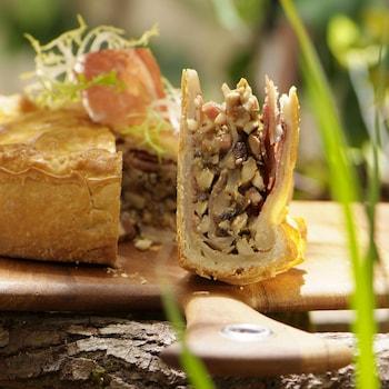 Tourte farcie de champignons bolets et de jambon sur une planche de bois.