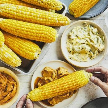 Trio de beurres aromatisés pour le maïs dans des assiettes avec plusieurs maïs.