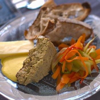 Un morceau de végé-pâté dans une assiette accompagné de légumes, de croûtons et d'une sauce jaune.