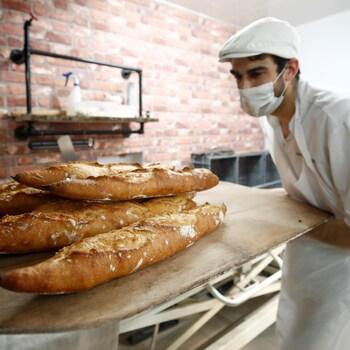 Le boulanger sort quelques baguettes d'un four.