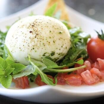 Une boule de fromage frais sur un lit de tomates et de verdures.