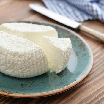 Une meule de fromage frais sur une assiette.