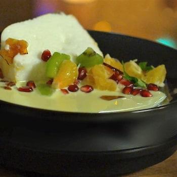 L'île flottante nappée de crème anglaise et ses petits fruits dans une assiette creuse,