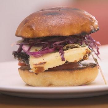Un burger au champignon et au fromage avec salade de chou dans une assiette.
