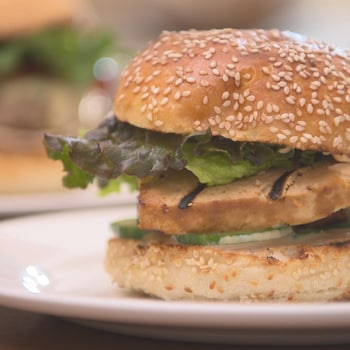 Un burger de tofu avec de la laitue dans une assiette.