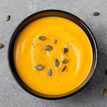 Un bol de soupe de courge parsemée de sel, de poivre et de graines de courge.