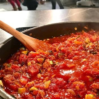 Une poêle remplie de sauce tomate avec une cuillère en bois.