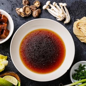 Plusieurs ingrédients disposés sur un comptoir gris : bouillon dans un petit bol, gingembre, champignons, salade et lime.