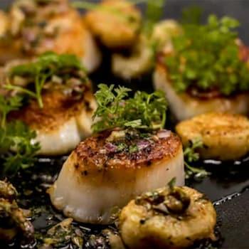 Pétoncles et gnocchis sur assiette noire.