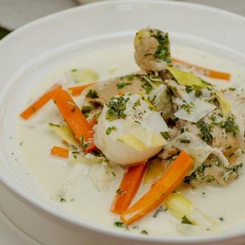 Le plat de waterzoï est présenté dans une assiette creuse sur la table.