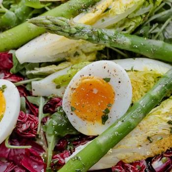 Une salade repas avec des œufs, des asperges et un mélange de laitues.
