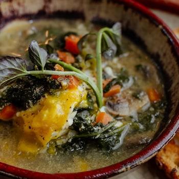 Une soupe repas avec des oeufs, du fromage ou du fauxmage, accompagnée de tranches de pain rôties.