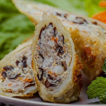 Une assiette de rouleaux impériaux au porc, garnie de laitue, carotte râpée et de coriandre.