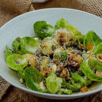 Une salade de choux de Bruxelles servie dans un grand bol blanc.