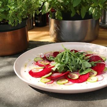 Carpaccio de betteraves, de concombres et de radis dans une assiette blanche.